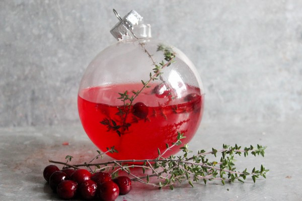 Christmas cocktail in a clear glass ornament! kellyelko.com #ornaments #christmascocktail #wintercocktail #cocktailrecipes