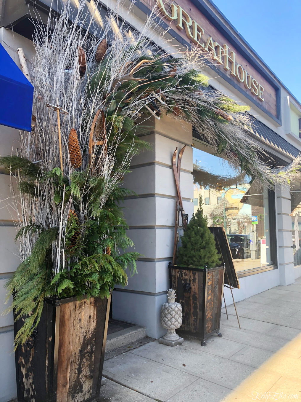 Wow this Christmas planter is incredible with branches stretching all the way across the storefront! kellyelko.com #planters #christmasplanter #christmasdisplays #christmasporch #planterideas #winterplanters #diychristmas #christmasdecor #kellyelko