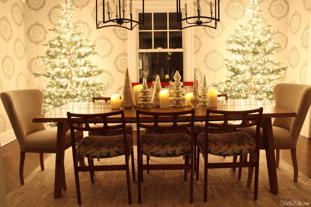 Christmas Nights Tour - love the two glowing trees in the dining room and the mercury glass centerpiece kellyelko.com #christmasdecor #christmastrees #christmasdiningroom #sparsechristmastree #christmaslights #cozychristmas #christmastable #christmascenterpiece #farmhousechristmas #fixerupperstyle #kellyelko #mercuryglass #danishmodern #eclecticstyle #wallmural