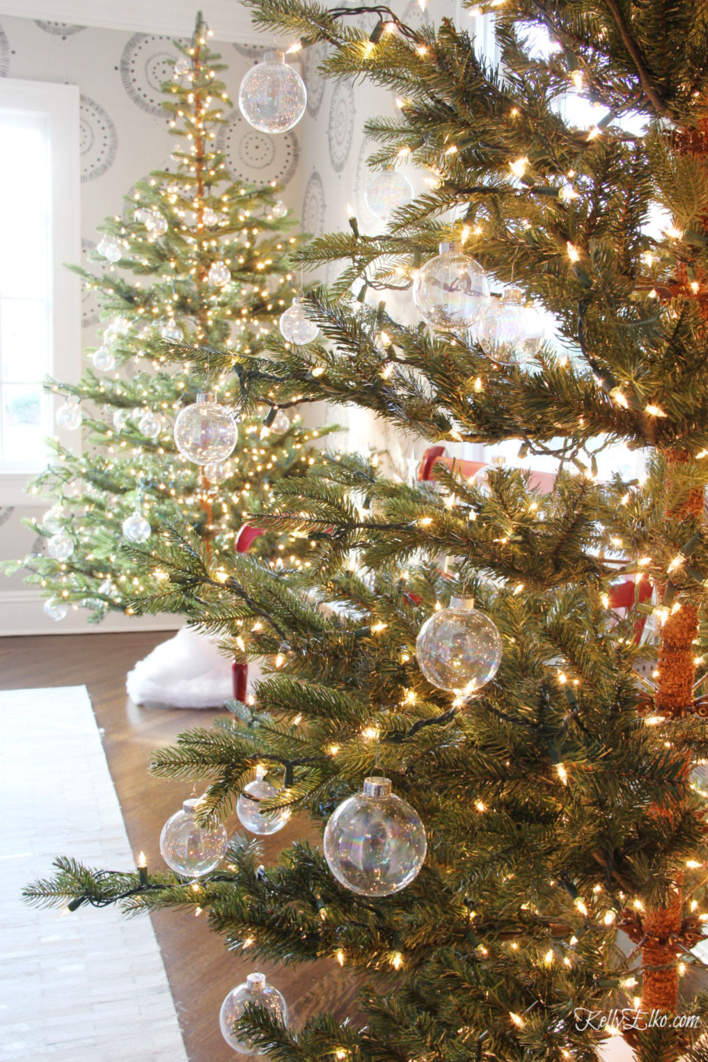 Beautiful Christmas Home Tour featuring a pair of sparse Christmas trees covered in clear glass ornaments kellyelko.com #christmas #christmasdecor #christmasdecorating #christmashome #christmastour #diychristmas #christmasideas #christmasmantel #christmastree #christmasornaments #vintagechristmas #farmhousechristmas #colorfulchristmas #creativechristmas #kellyelko