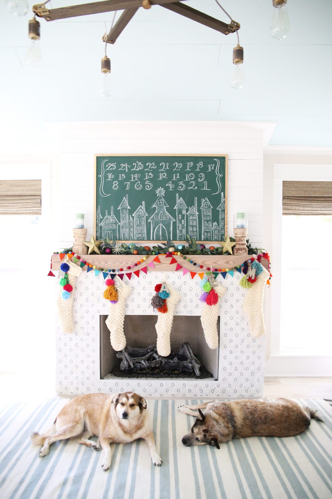 Love this colorful Christmas mantel and chalkboard Advent calendar #colorfulchristmas #christmasdecor #christmasmantel #adventcalendar #chalkart #christmaschalkart