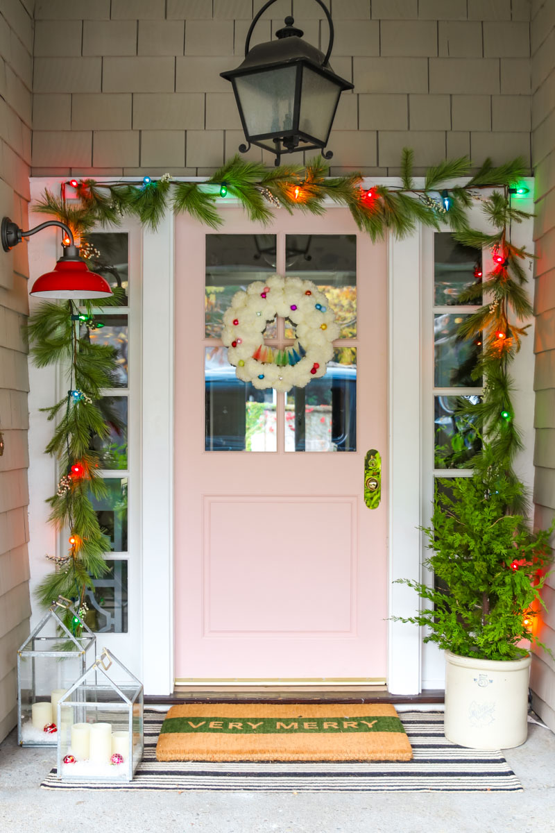 Festive and colorful Christmas porch with pink door #christmas #christmasdecor #christmasporch #pinkdoor #christmasgarland #christmaslights
