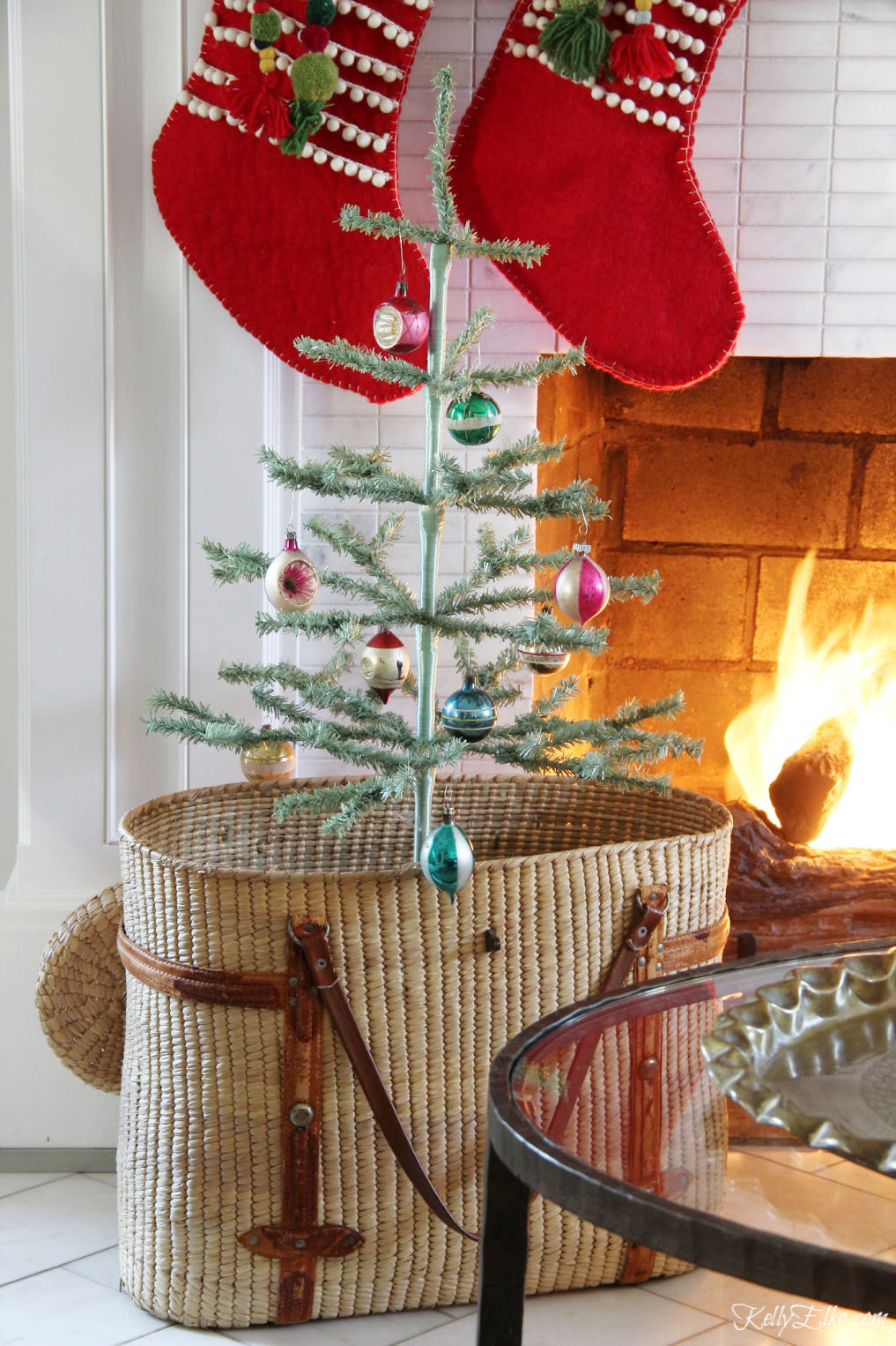 Beautiful Christmas mantel with feather trees in a basket and red stockings kellyelko.com #christmas #christmasdecor #christmasdecorating #christmashome #christmastour #diychristmas #christmasideas #christmasmantel #christmastree #christmasornaments #vintagechristmas #farmhousechristmas #colorfulchristmas #creativechristmas #kellyelko
