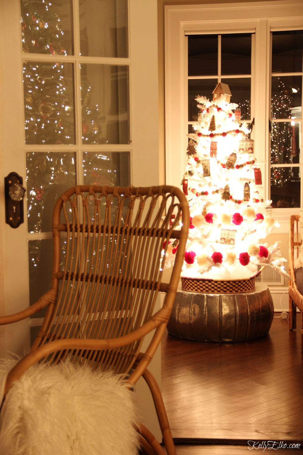 Tour this Christmas home by the glowing lights at night with a beautiful white tree kellyelko.com #christmasdecor #christmastree #whitetree #whitechristmastree #christmasglow #christmaslights #farmhousechristmas #farmhousedecor #rattanfurniture #kellyelko