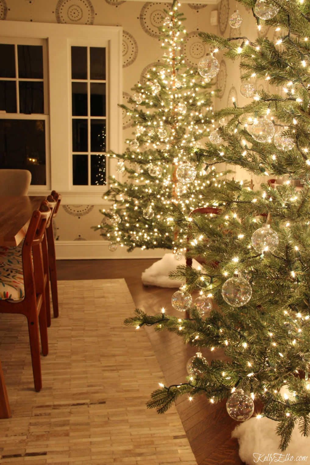 Glowing Christmas Tour at Night - love the pair of glowing sparse trees with clear glass ornaments kellyelko.com #christmasdecor #christmastrees #sparsechristmastrees #christmaslights #christmasdiningroom #christmasornaments #clearornaments #diychristmas #christmascrafts #kellyelko #farmhousechristmas #fixerupperstyle