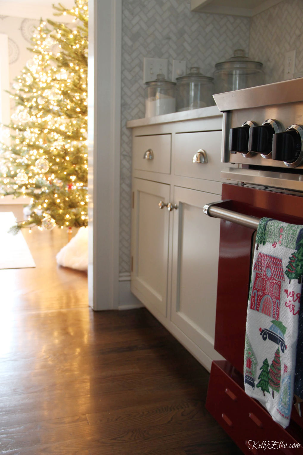Christmas Home Tour - love the red stove and the twinkling Christmas trees kellyelko.com #christmas #christmasdecor #christmasdecorating #christmashome #christmastour #diychristmas #christmasideas #christmasmantel #christmastree #christmasornaments #vintagechristmas #farmhousechristmas #colorfulchristmas #creativechristmas #kellyelko #christmaskitchen #redstove