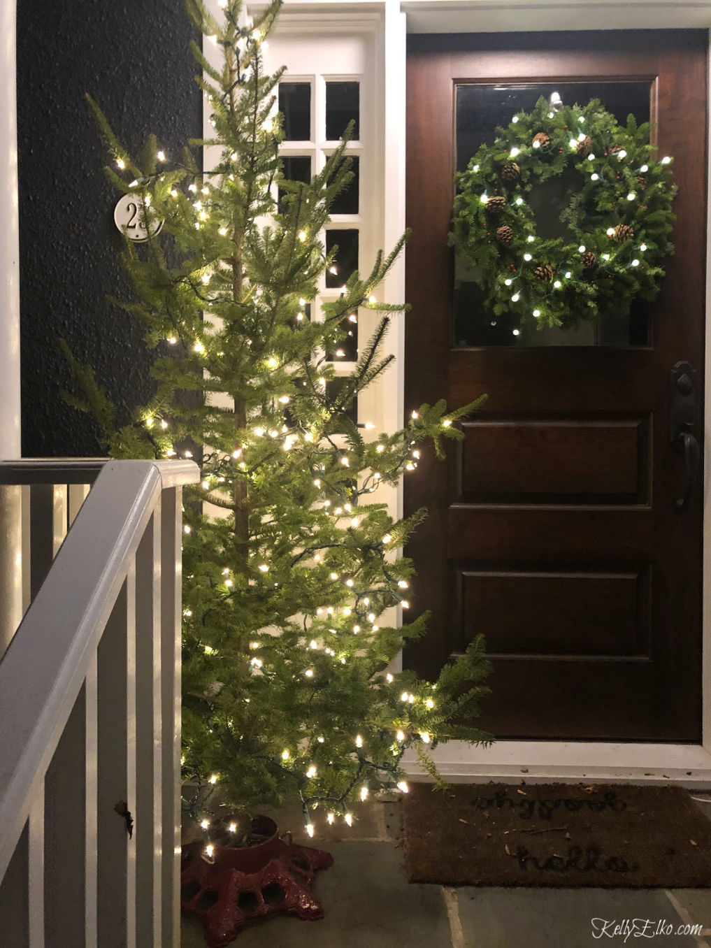 Love this real Christmas tree on the front porch kellyelko.com #christmastree #livechristmastree #christmasporch #christmasporchdecor #christmaslights #sparsetree #kellyelko