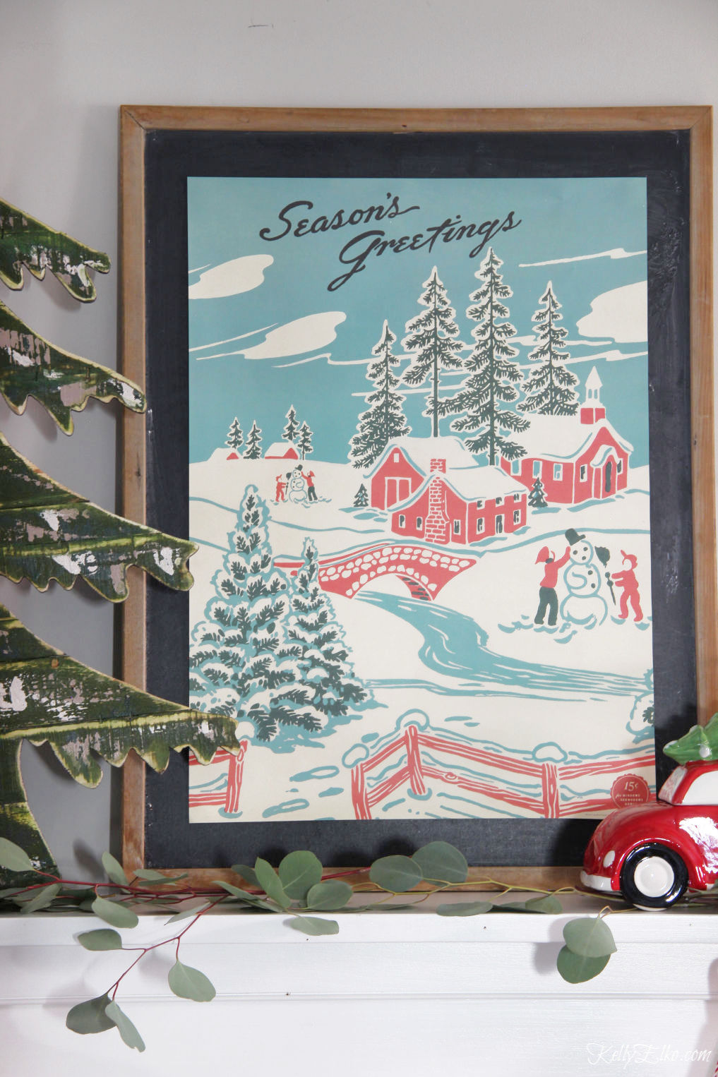 Beautiful Christmas Art of a little winter village with red barn kellyelko.com #christmas #christmasdecor #christmasdecorating #christmashome #christmastour #diychristmas #christmasideas #christmasmantel #christmastree #christmasornaments #vintagechristmas #farmhousechristmas #colorfulchristmas #creativechristmas #kellyelko #christmasart