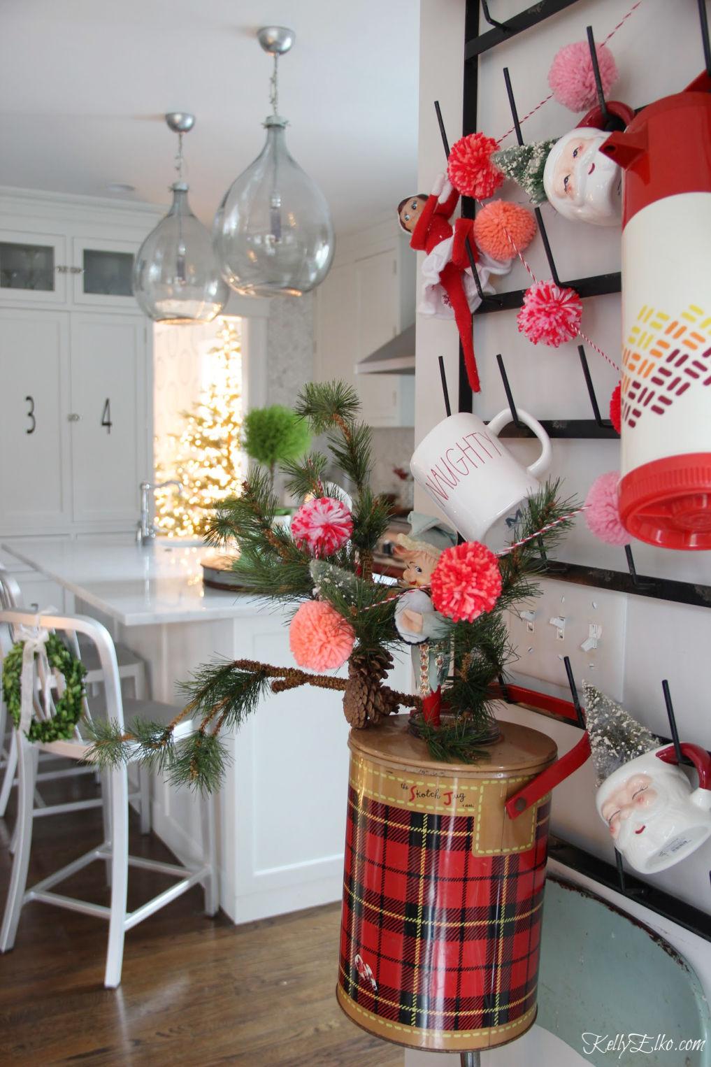 Colorful Christmas Home Tour - love this wall rack displaying vintage Christmas finds kellyelko.com #christmas #christmasdecor #christmasdecorating #christmashome #christmastour #diychristmas #christmasideas #christmasmantel #christmastree #christmasornaments #vintagechristmas #farmhousechristmas #colorfulchristmas #creativechristmas #kellyelko #vintagedecr #santamugs #santa #elves #christmaskitchen