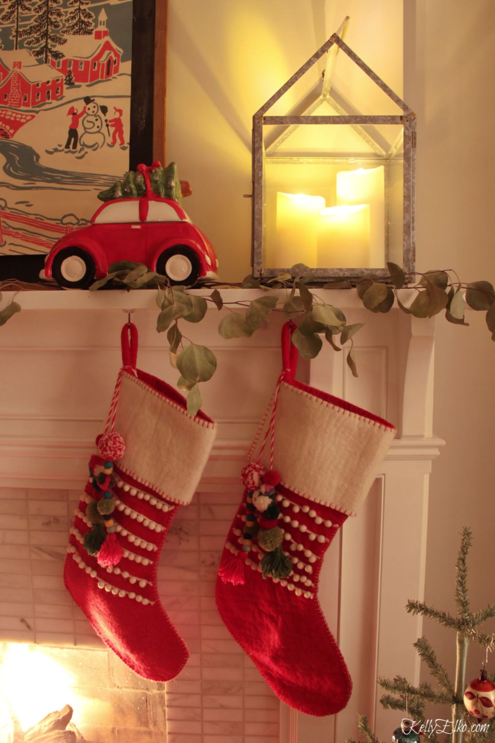Christmas Night Tour - love the lanterns with candles and the pom pom stockings on the mantel kellyelko.com #christmasdecor #christmasmantel #christmasstockings #vintagechristmas #colorfulchristmas #farmhousechristmas #kellyelko