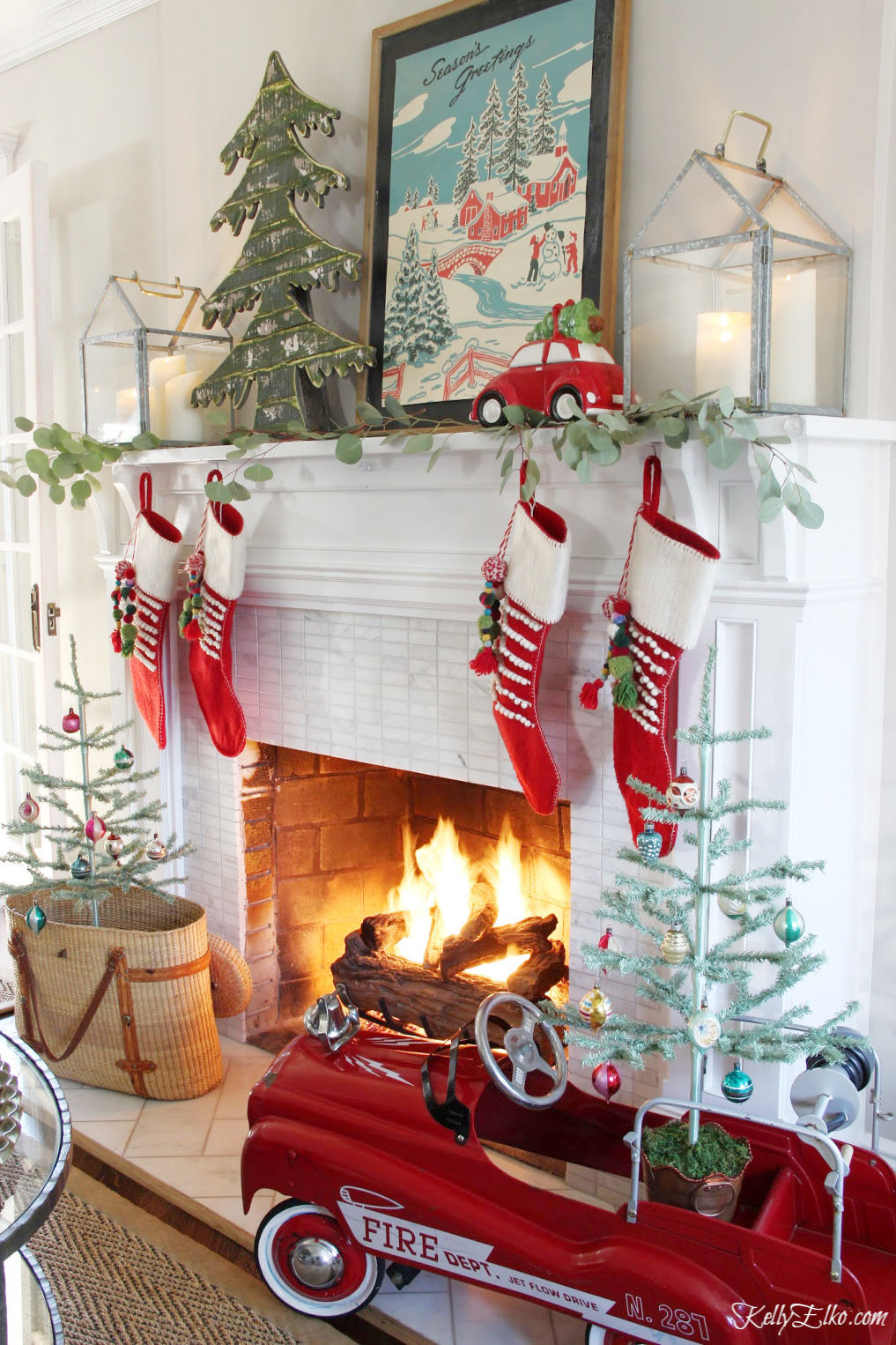 Festive Christmas Decorating Ideas - love this whimsical mantel with vintage firetruck pedal car and red stockings kellyelko.com #christmas #christmasdecor #christmasmantel #christmasstockings #vintagechristmas #feathertrees #fireplace #kellyelko