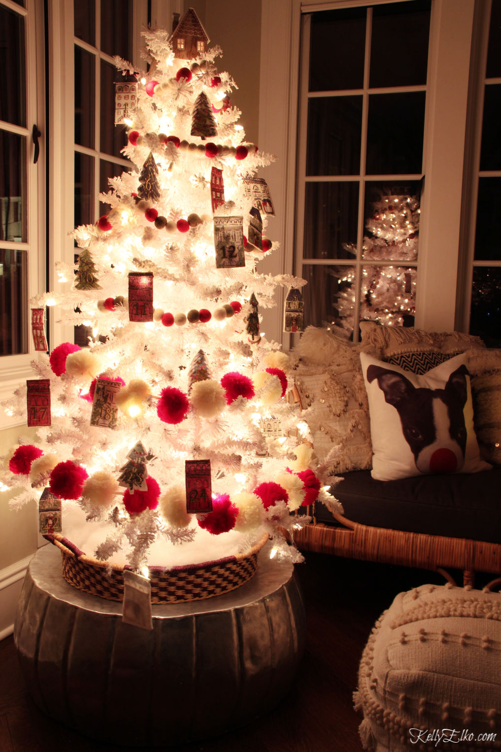 Glowing white Christmas tree with whimsical red pom pom garland kellyelko.com #christmasdecor #christmastree #whitechristmastree #whitetree #adventtree #adventcalendar #farmhousechristmas #whimsicalchristmas #farmhousechristmas #farmhousedecor #kellyelko