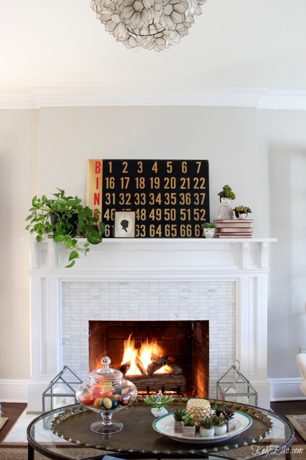 Vintage modern mantel decor - love the huge old bingo board and black white red and green color palette kellyelko.com #mantel #manteldecor #vintagedecor #vintagemantel #wintermantel #vintagedecorating #thriftedecor #thriftydecor #plantlady #houseplants #succulents #farmhousemantel #farmhousedecor #eclecticdecor #fireplacedecor #kellyelko
