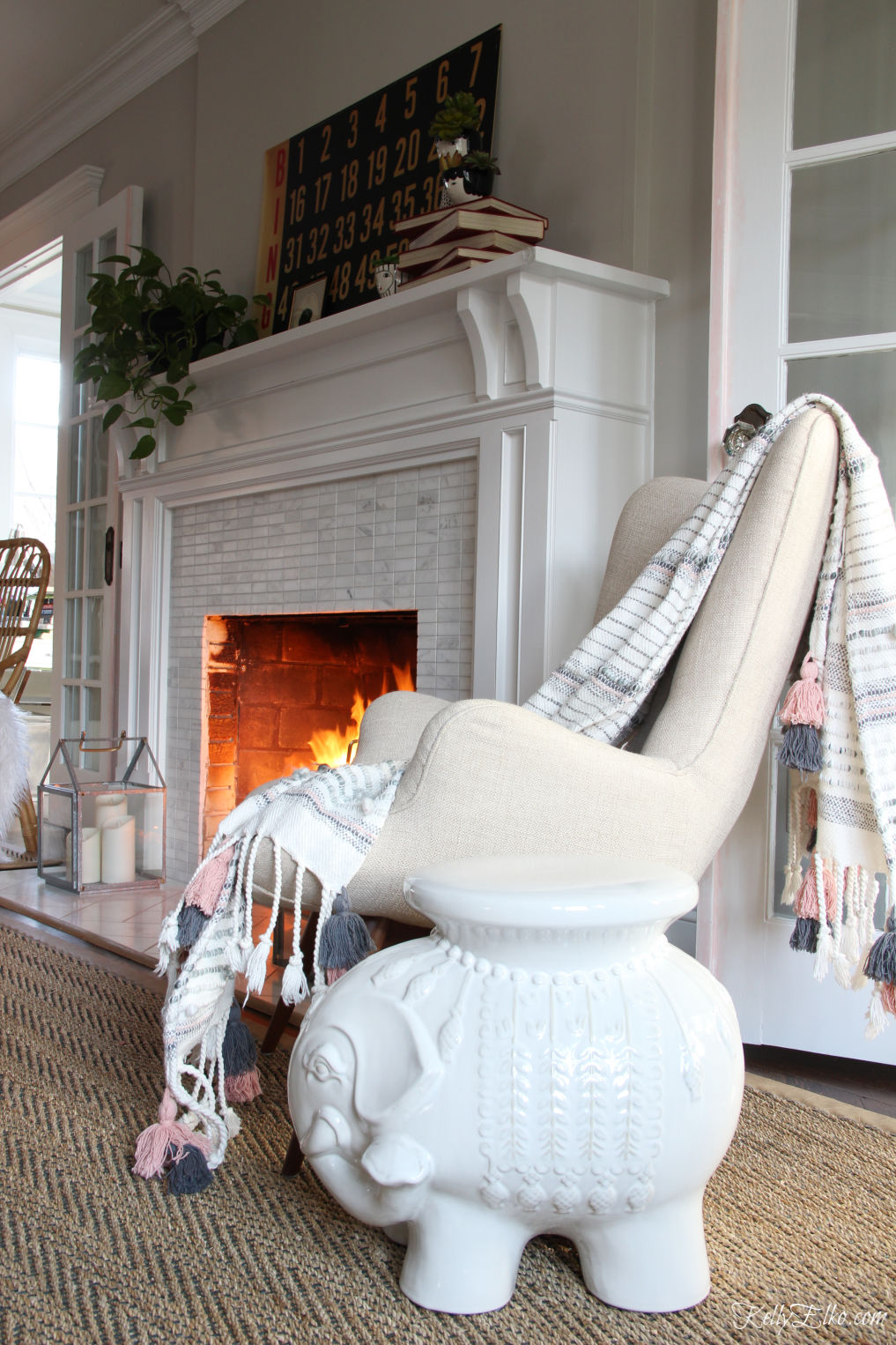 Love this mantel in black and white with a vintage bingo scorecard and the adorable elephant stool and tassel throw kellyelko.com #livingroomdecor #bohodecor #eclecticdecor #elephant #vintagemodern #mantel #manteldecor #fixerupperstyle #farmhousedecor #kellyelko.com #fireplacedecor #cozydecor