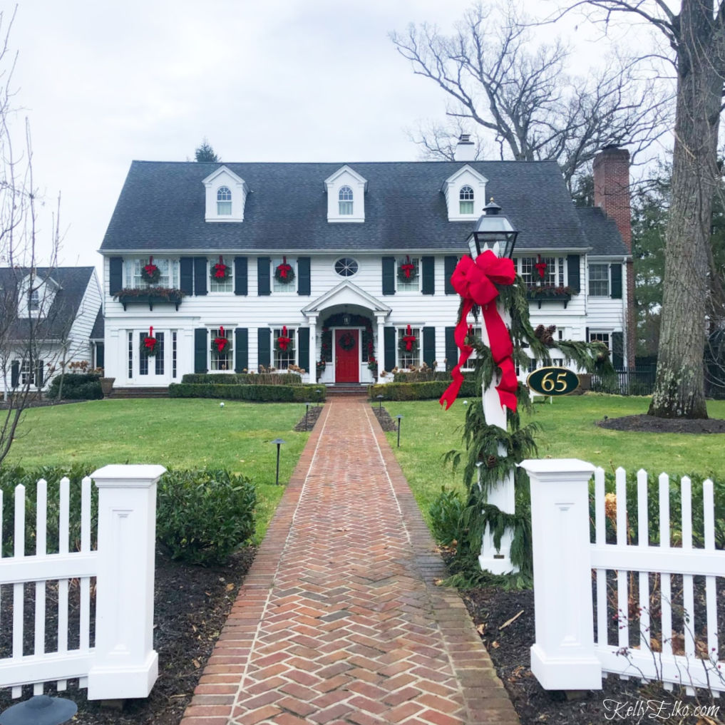 Classic white house with black shutters decked out for Christmas. Love the outdoor wreaths with festive red bows kellyelko.com #christmas #christmasdecor #outdoorchristmasdecor #christmashouse #christmaswreath #classicchristmas #christamsdecoratingideas #outdoorchristmasdecorations #kellyelko #oldhouse