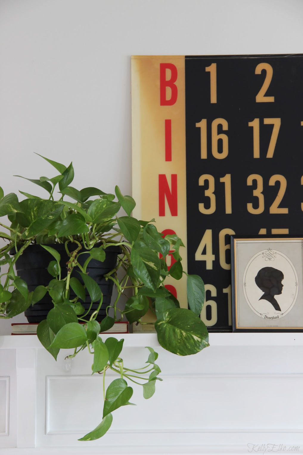 Love this vintage inspired mantel in black and white with touches of green from a pothos plant kellyelko.com #mantel #manteldecor #pothos #houseplants #plantlady #vintagedecor #vintagemantel #silhouette #bingo #thriftydecor #thrifteddecor #vintagemodern #farmhousedecor #kellyelko