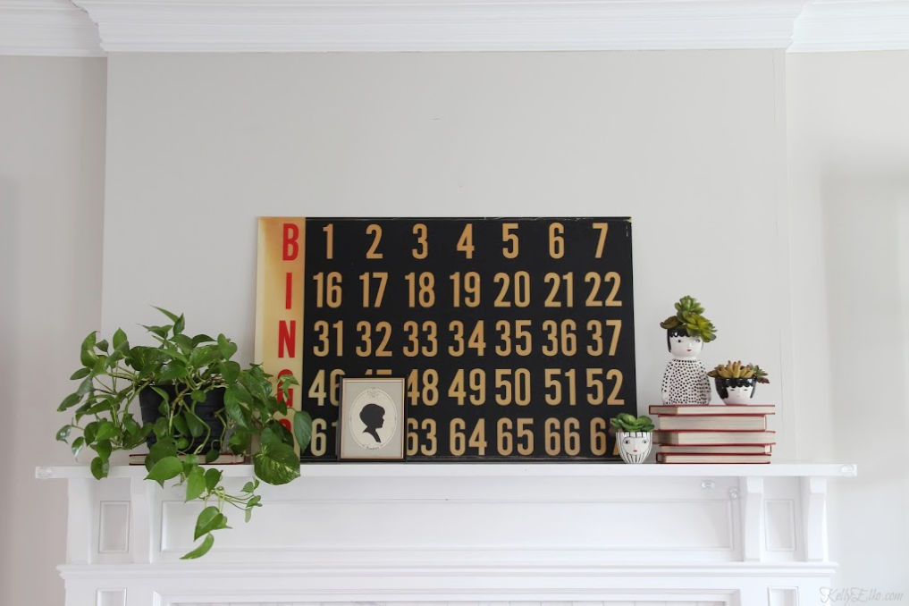 Love this eclectic vintage modern mantel with an old Bingo scoreboard, plants and face planters kellyelko.com #vintagemodern #vintagedecor #farmhousedecor #fixerupperstyle #plantlady #pothos #houseplants #succulents #thrifteddecor #thrifted #thrifty #kellyelko