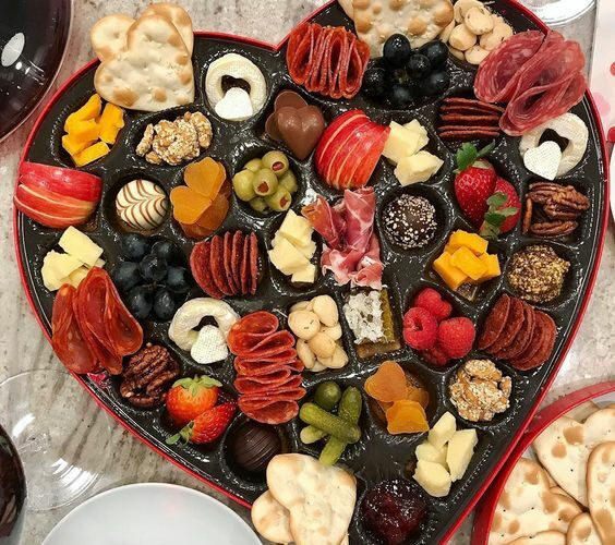 Simple Valentine Ideas - love this Valentine candy box turned charcuterie board kellyelko.com #charcuterie #valentine #valentinesday #snackboard #appetizers #partyfood #valentinesfood #valentinesparty