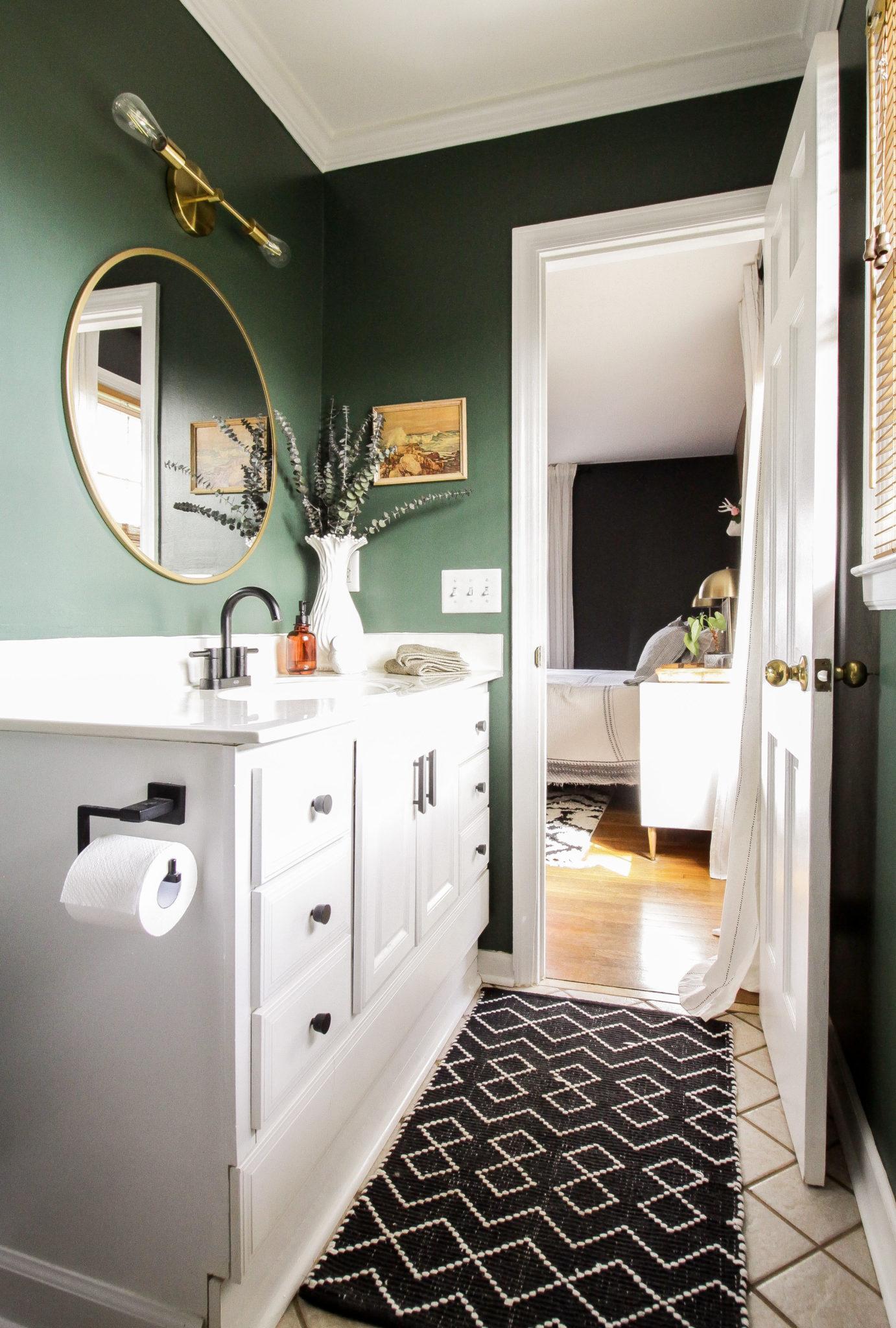 Hunter green bathroom with brass fixtures