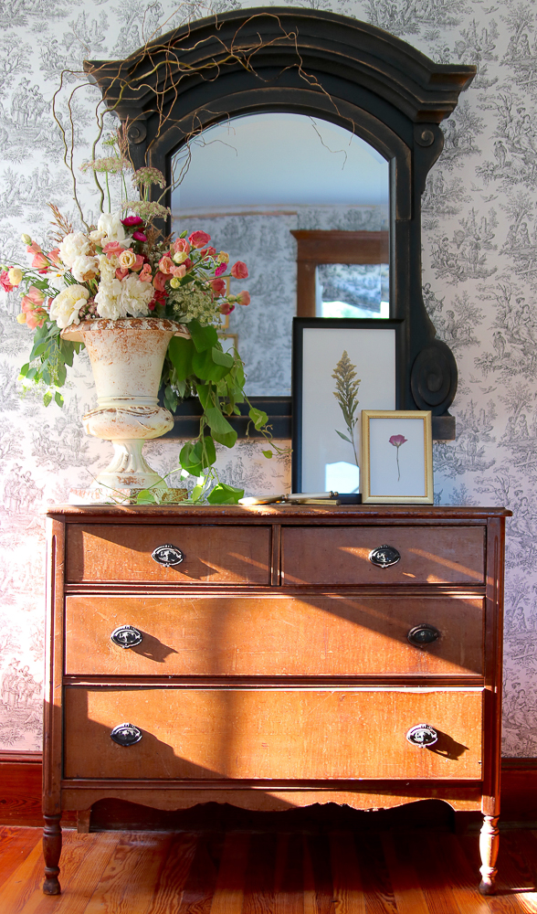 Toile wallpaper is a beautiful backdrop to an antique chest and mirror kellyelko.com #toile #antiques #farmhouse #farmnousedecor #antiquedresser #urn #floralarrangement #countryliving