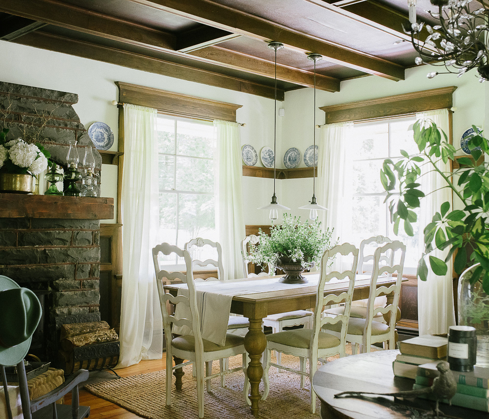 Coffered ceilings in dark wood contrast with white dining chairs and an original old stone fireplace in this charming farmhouse dining room kellyelko.com #diningroom #diningroomdecor #farmhouse #farmhouserdecor #antiques #fireplace #mantel