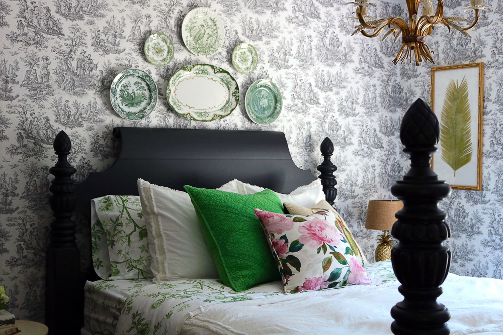 Toile wallpaper is the perfect backdrop to a green plate wall in this guest bedroom kellyelko.com #bedroom #antiquebedroom #farmhouse #farmhousedecor #farmhousebedroom #platewall #antiquebed #antiquefurniture #toile #toilewallpaper