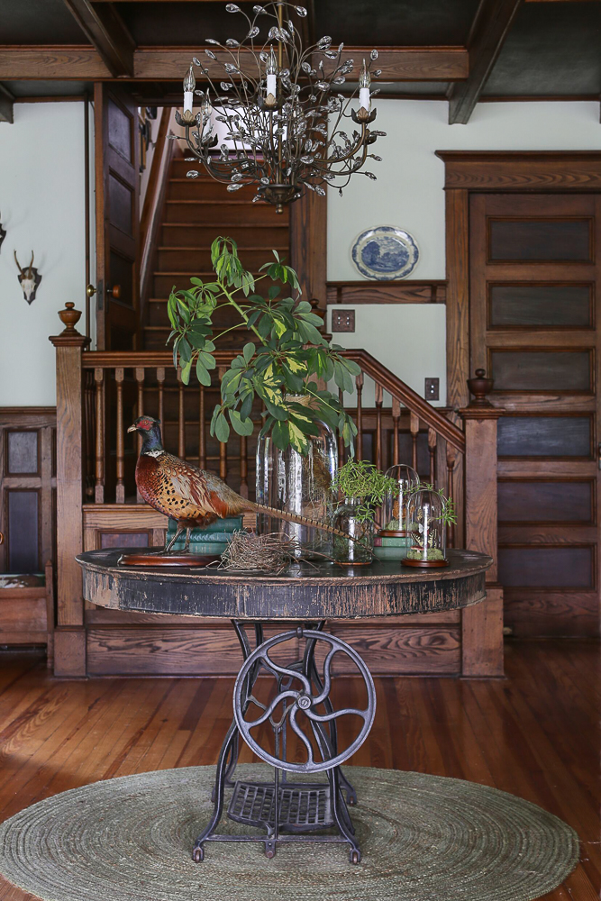 Tour this charming farmhouse filled with original walnut wood trim and an eclectic mix of furniture and accessories including a taxidermy pheasant and crystal chandelier kellyelko.com #rusticdecor #farmhouse #farmhousedecor #oldhome #antiquehouse #farmhouse #farmhousedecor #countryliving #vintagemodern #pheasant #taxidermy #fixerupper #fixerupperstyle #antiques