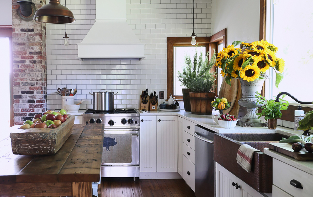 Love this charming farmhouse kitchen with wood table as an island and subway tile to the ceiling kellyelko.com #kitchen #countrykitchen #farmhousekitchen #farmhouse #farmhousedecor #sunflowers #subwaytile #backsplash