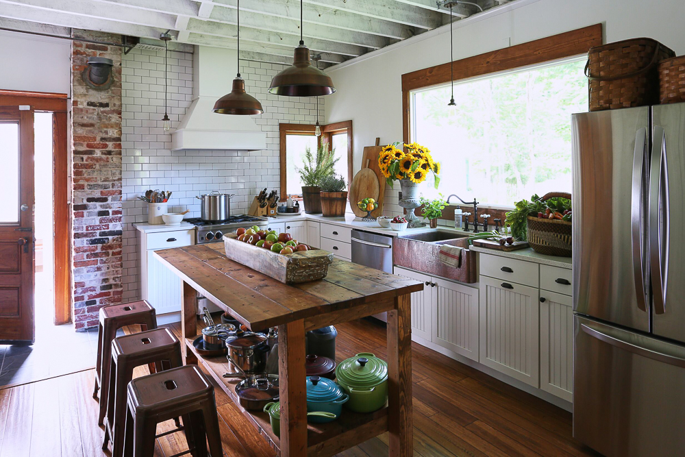 Charming farmhouse kitchen with subway tile backsplash, copper farmhouse sink, wood table island and exposed brick kellyelko.com #kitchen #kitchendecor #farmhouse #farmhousedecor #farmhousekitchen #countrykitchen #countryliving #kitchenisland #rustickitchen #oldhouse #housetour