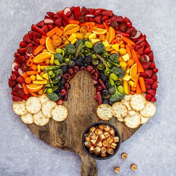 How fun is this rainbow charcuterie snack board filled with colorful fruits and vegetables - perfect for St Patrick's Day #stpatricksday #partyfood #rainbow #appetizers #snacks #snackboard #charcuterie #charcuterieboard