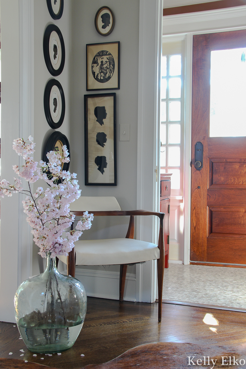 Love the graphic punch these vintage silhouettes add to this foyer kellyelko.com #foyer #foyerdecor #art #vintageart #silhouettes #vintagesilhouettes #eclecticdecor #farmhousedecor #cherryblossom #floweringbranches #midcenturydecor #oldhouse #oldhome #vestibule