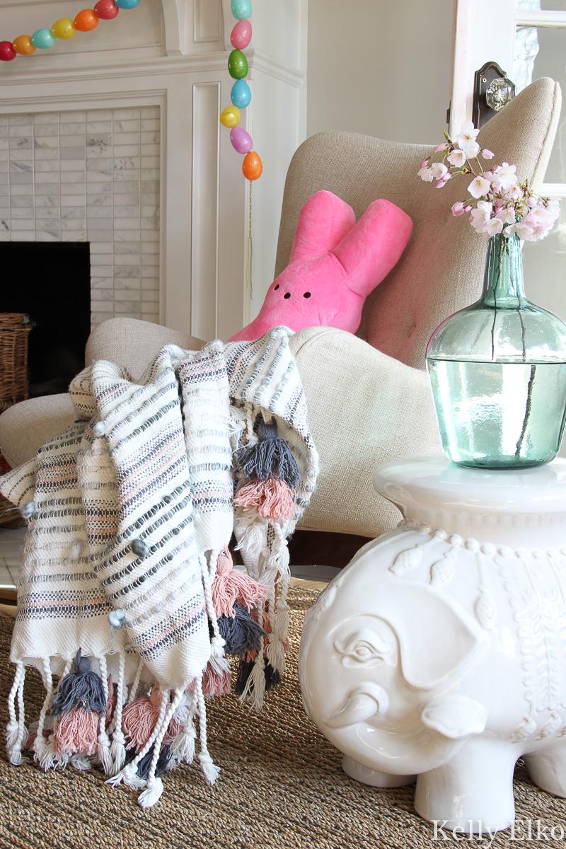 Love this spring decor with tassel throw and pink Peep pillow! kellyelkol.com #spring #springdecor #bohodecor #tassels #peeps #elephantdecor #eclecticdecor #easterdecor #kellyelko #cherryblossom