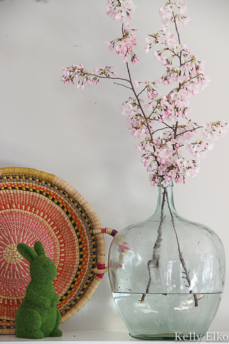 Beautiful spring mantel with flowering cherry blossom branches in a vintage glass jug kellyelko.com #spring #springdecor #cherryblossom #floweringtrees #floweringbranch #bohodecor #easterbunny #vintagedecor #farmhousedecor