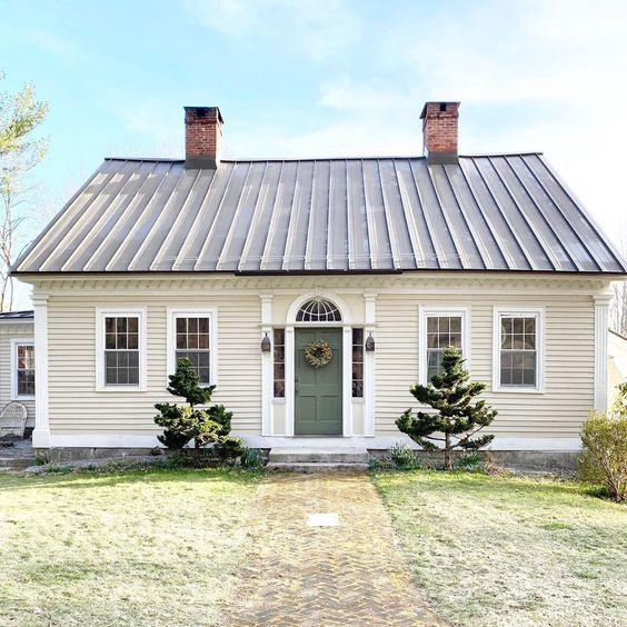 Antique 1800's Cape with metal roof and arched window over the boxwood green front door #cape #antiquehome #antiquehouse #oldhomes #oldhouse #metalroof #housetour #hometour