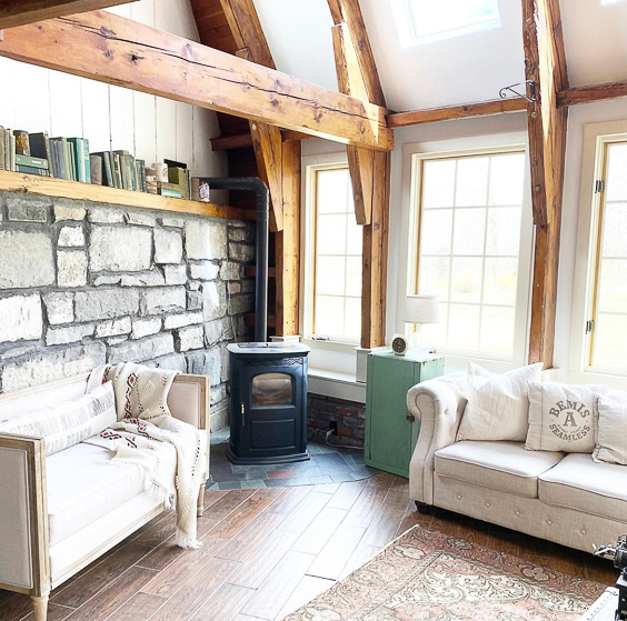 Love the wood beams in this farmhouse family room #woodbeams #familyroom #familyroomdecor #farmhouse #farmhousedecor #neutraldecor #cozydecor #stone #stonewall