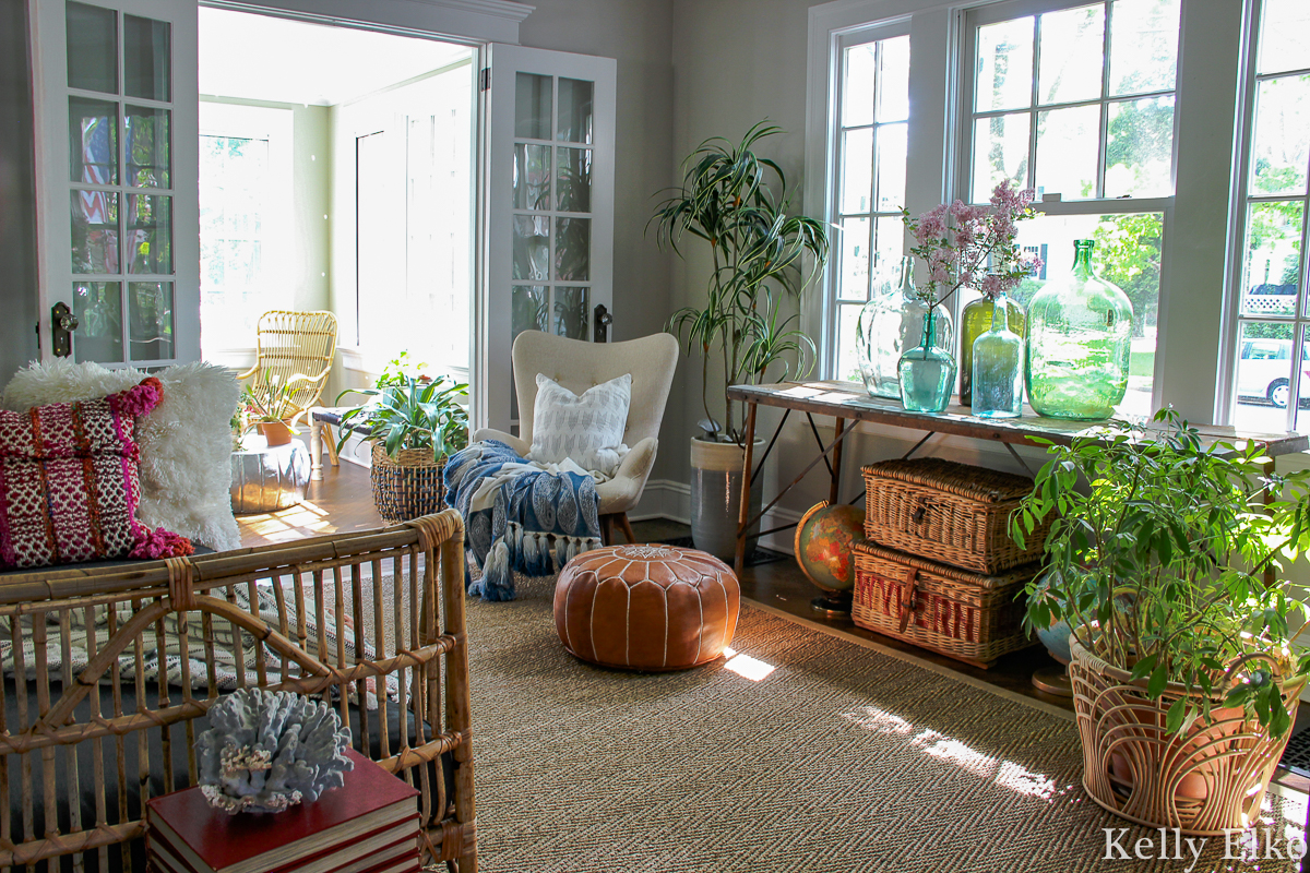 Eclectic boho living room filled with plants, vintage finds and lots of texture from rattan, leather tassels, wicker and more kellyelko.com #vintagedecor #eclecticdecor #bohodecor #livingroomdecor #plantlady #houseplants #vintagecollections #collections #vintageglass #demijohn #rattan #daybed #interiordecor #interiorstyling #cozydecor #kellyelko