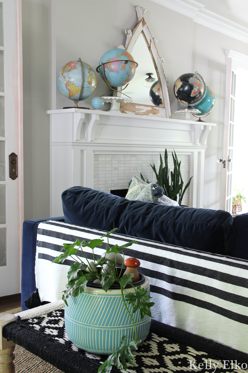 Eclectic living room with vintage globe collection and lots of boho texture from tassel throws and woven benches and plants kellyelko.com #vintagedecor #eclecticdecor #bohodecor #plantlady #houseplants #collections #vintagecollection #globes #manteldecor #farmhousedecor #interiordecor #manteldecor