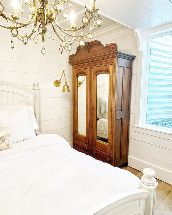 Farmhouse white bedroom with shiplap walls, brass lighting and antique hutch kellyelko.com #hutch #antique #antiquefurniture #farmhouse #farmhousedecor #farmhousebedroom #shiplapbedroom #whitebedroom #neutraldecor #vintagedecor #brasslighting