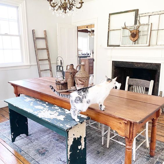 Charming farmhouse dining room with mismatched table and chairs and a mantel of antique mirrors #antiques #vintage #diningroom #diningroomdecor #diningroomfurniture #vintagedecor #vintagefurniture #manteldecor #farmhouse #farmhousedecor #farmhousediningroom #fixerupperstyle #shabbychic
