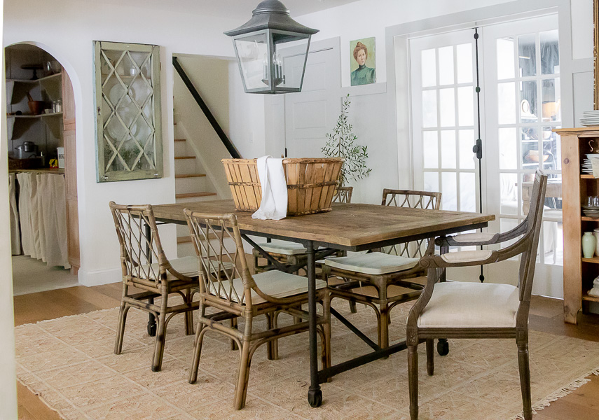 Beautiful farmhouse dining room with large iron lantern, wood, metal and rattan furniture #farmhouse #farmhousedecor #farmhousediningroom #diningroom #neutraldecor #neutraldiningroom #diningroomlighting #farmhouselighting #vintagedecor #rattan