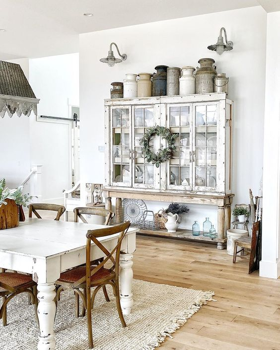 Eclectic Home Tour of Sweet Pickins - love the collection of vintage milk cans kellyelko.com #farmhouse #farmhousedecor #housetour #hometour #farmhousestyle #vintagedecor #vintage #collections #milkcans #neutraldecor #vintagediningroom #farmhousediningroom #galvanized #sconces #hutch