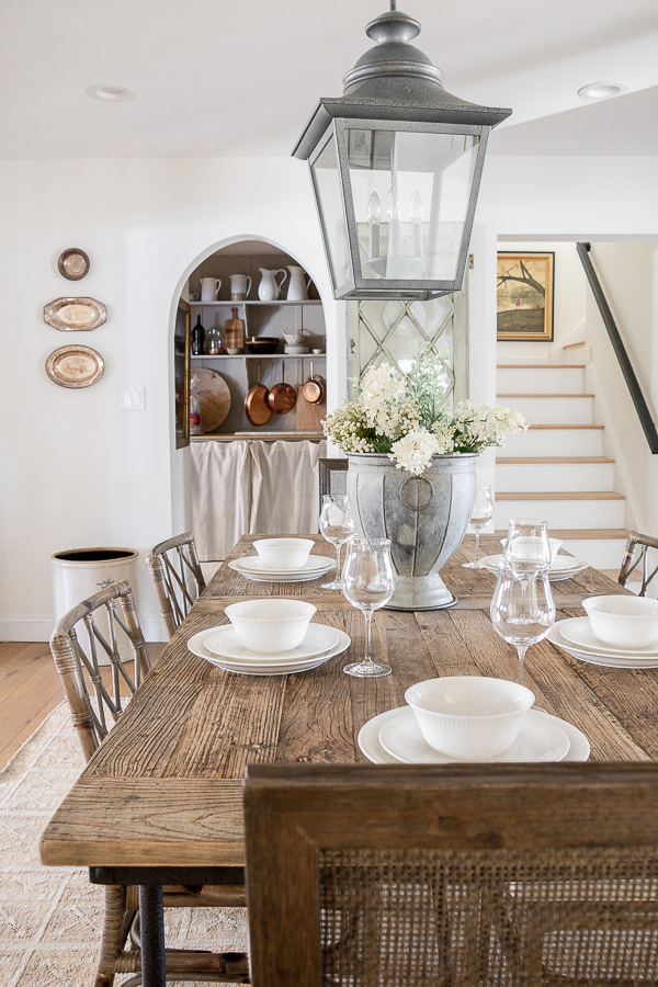 A huge lantern adds drama to this farmhouse dining room #lighting #farmhouse #farmhousedecor #farmhouselighting #lantern #farmhousediningroom #neutraldecor #frenchdecor #vintagedecor #rattan