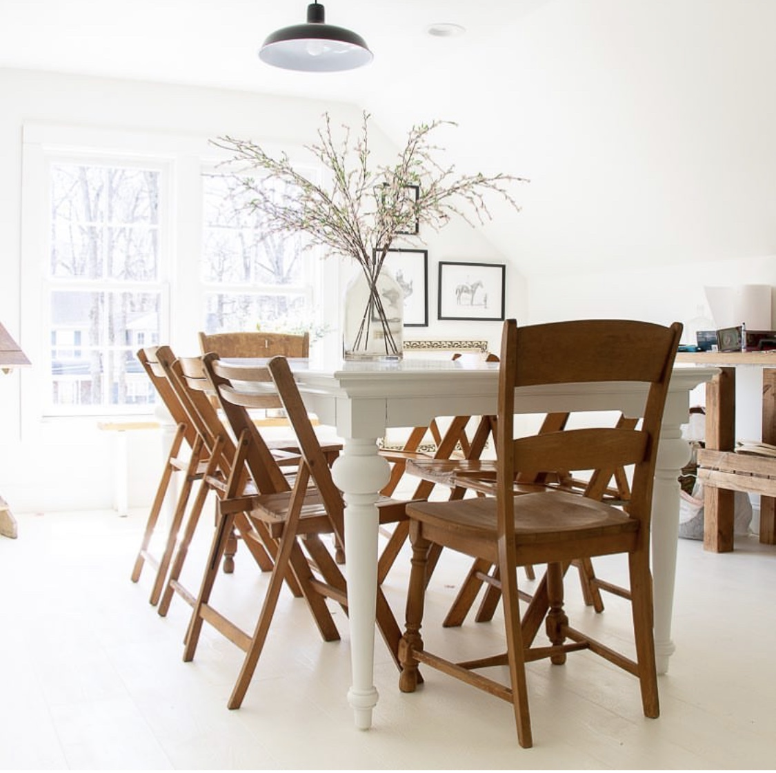 Love this all white home office craft studio with vintage wood folding chairs and industrial light #office #homeoffice #studio #craftroom #crafting #vintage #vintagedecor #neutraldecor #farmhouse #farmhousedecor