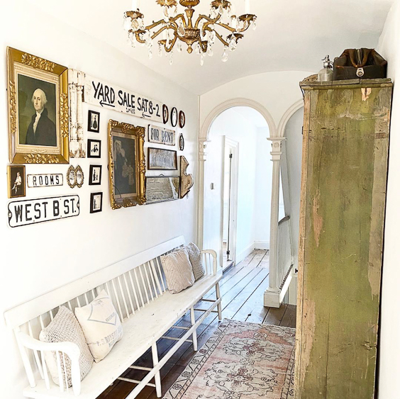 Tour this charming old home with an entry filled with antique finds like this chippy green cabinet and white bench #foyer #entry #farmhousedecor #farmhousefoyer #vintagedecor #vintage #antiques #gallerywall #fixerupperstyle