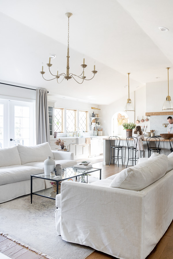 Love this open floor plan and matching slipcovered sofas #slipcovers #familyroom #lighting #chandelier #farmhouse #farmhouseecor #neutraldecor