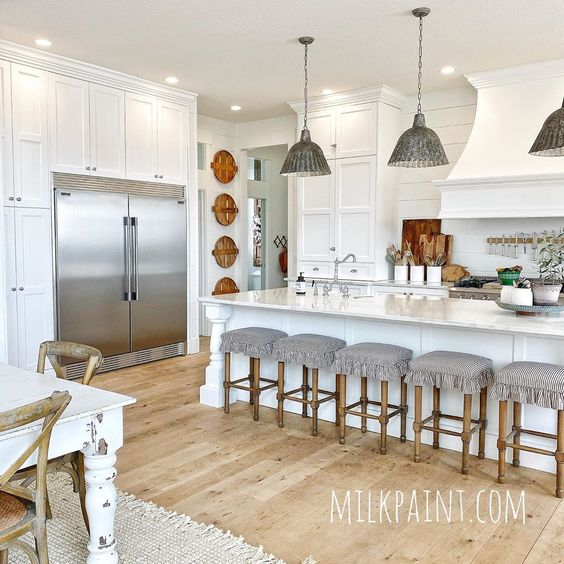 Love this beautiful farmhouse white kitchen with galvanized metal lighting and basket wall art kellyelko.com #farmhouse #farmhosuekitchen #farmhousedecor #whitekitchen #kitchenlighting #kitchenisland #vintagedecor #kitchenstools #shiplap