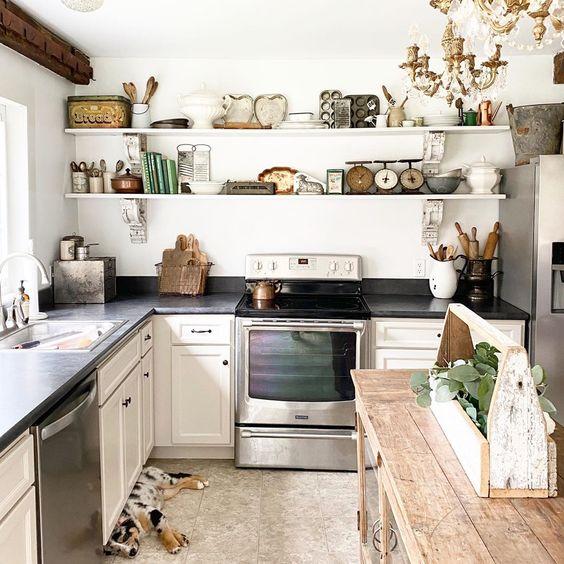 Charming farmhouse kitchen with open shelves held up by antique corbels #kitchen #farmhousekitchen #farmhousedecor #kitchendecor #vintagedecor #openshelves #shelfie #shelfstyling #kitchenisland