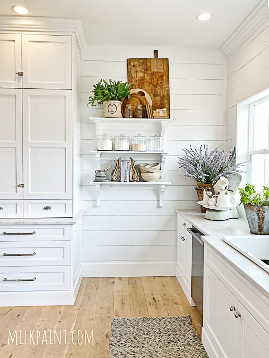 Love the open kitchen shelves for display in this farmhouse kitchen kellyelko.com #farmhouse #farmnhousedecor #farmhousekitchen #openshelves #breadboard #shiplap #vintagedecor #farmhousesink #fixerupper
