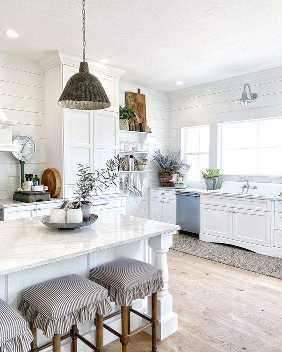 Beautiful white farmhouse kitchen with galvanized lighting and beautiful farmhouse sink kellyelko.com #farmhouse #farmhousedecor #farmhousesink #whitekitchen #shiplap #farmhouselighting #lighitng #fixerupper #neutraldecor