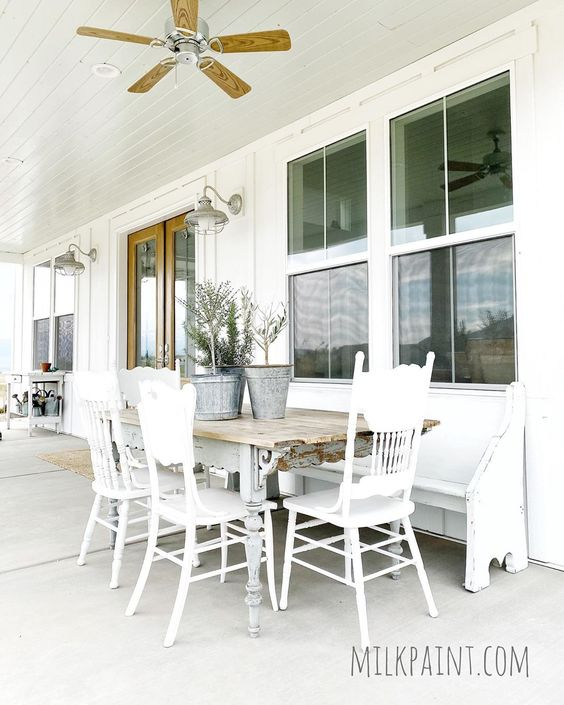 Beautiful farmhouse porch with milk paint vintage table and chairs kellyelko.com #farmhouse #farmhousefurniture #farmhouseporch #farmhousedecor #vintagedecor #vintagefurniture #porch #porchdecor #churchpew #paintedfurniture #diyideas